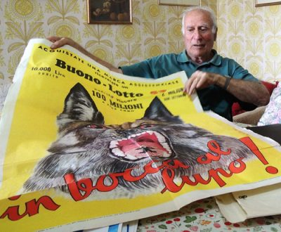 """Michele Arcangelo Jocca mostra il manifesto della lotteria """"In bocca al lupo"""" da lui creata nel 1952"""
